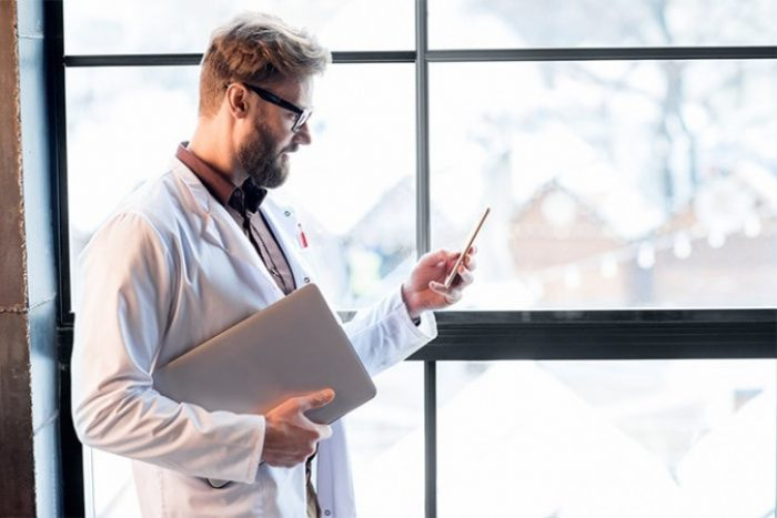 Man in lab coat holding a laptop computer while looking at a mobile phone.